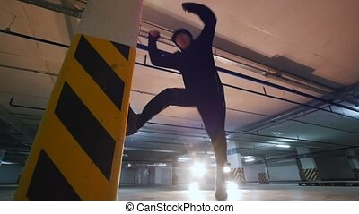 Young stylish guy freerunner doing a flip from the wall in...