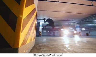 Young stylish guy freerunner doing a series of jumps, flips,...
