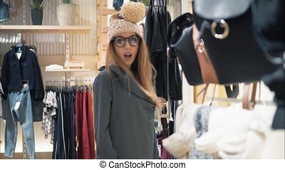 Young stylish hipster woman trying on caps in the store and flirting