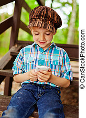 Young stylish kid playing games on mobile phone