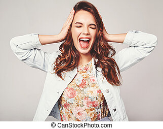 young stylish laughing girl model in colorful casual summer clothes with natural makeup isolated on gray background. Looking at camera and screaming with hands near head