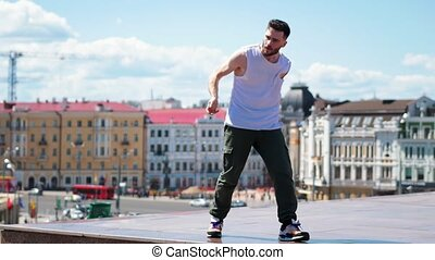 Young stylish man freestyle dancing on the top point in the...