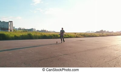 Young stylish man freestyle dancing under the bridge by the...