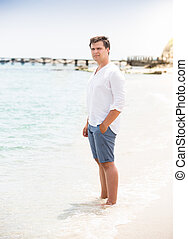 stylish man in shirt and shorts standing on the beach