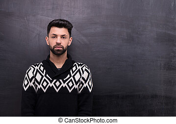 Young stylish man on blank chalkboard background