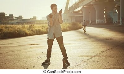 Young stylish man performing freestyle dancing - sunset. Mid...