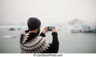 Young stylish man standing on the shore in Jokulsalon ice...
