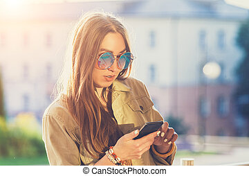 Young stylish pretty Woman, hands holding a phone, denim shirt and jeans, Sunset background, hat, backpack, Sunny day, good weather, Tropical mood, detail, cool accessories