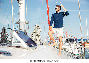 Young stylish sailor man standing on the yacht
