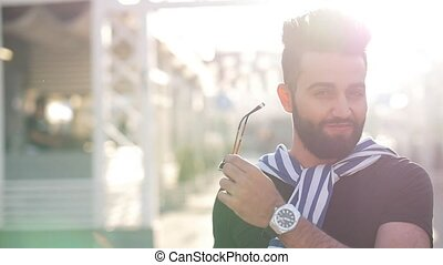 young stylish smiling arabic or latin man on a city street