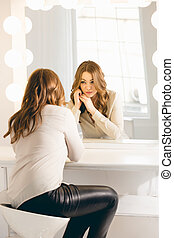 stylish woman looking in her reflection at mirror with bulbs