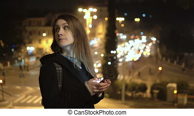 Young stylish woman standing near the traffic road in the late evening and using the smartphone with touchscreen.