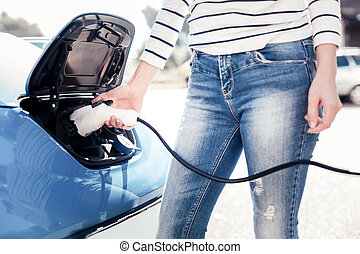 Young stylish woman staying and charging the car.