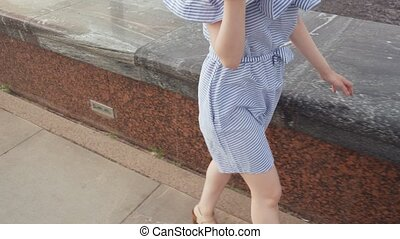 Young stylish woman walking on the waterfront in the city....