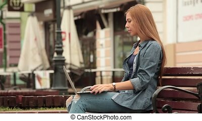 Young stylish woman with a laptop is sitting on a bench and working.