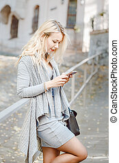 Young stylish woman with smart phone the street