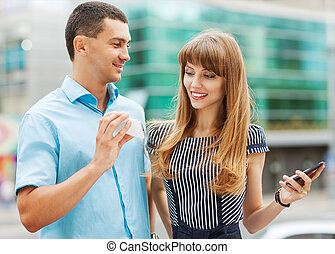 Young stylishly dressed couple on the street. He shows her ...
