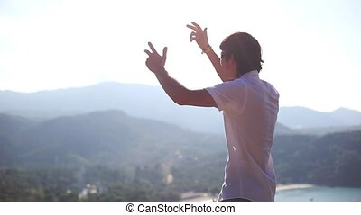 Young succesful businessman standing on top of a mountain...