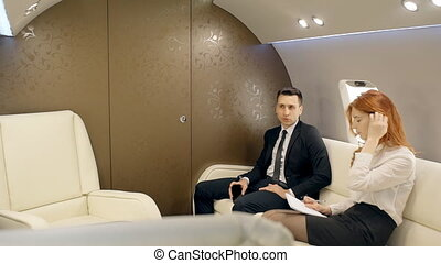 Young successful businessman and female employee working in private jet during flight.