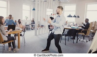 Young successful businessman doing victory dance in modern light multi-ethnic office, people clapping and laughing 4K.