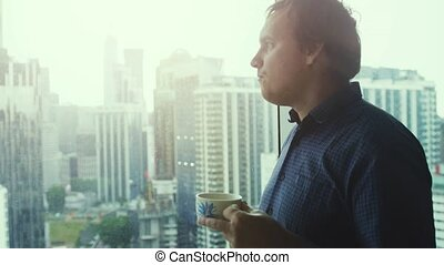 Young successful businessman drinking coffee and admire view...