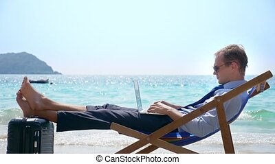 Young successful businessman is sitting on a lounger on a white sandy beach against the turquoise sea and using his laptop. his legs lie on a suitcase with hand luggage