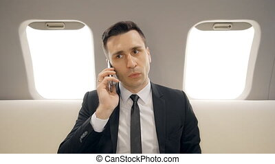Young successful businessman is talking on phone sitting in airplane interior.