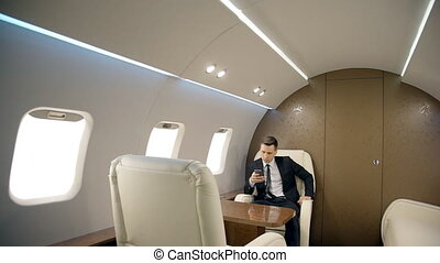 Young successful businessman is using smartphone while sitting in private plane.