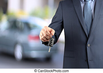 Young successful businessman offering a car key. Close-up of dri