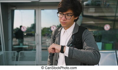 Young Successful Businessman Standing in the City. Looking at his Stylish Watch.
