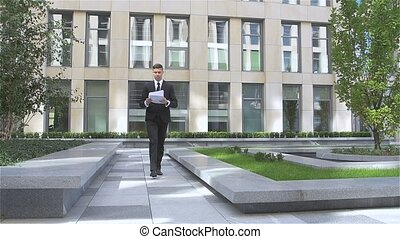 Young successful businessman throwing paper with arms in the air, slow motion
