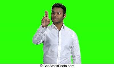 Young successful businessman touching virtual screen.