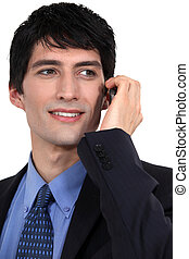 Young successful businessman using mobile telephone