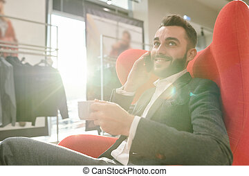 Young successful businessman with cup of tea consulting client by mobile phone
