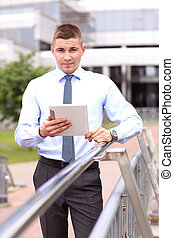 Young successful businessman with tablet outdoors