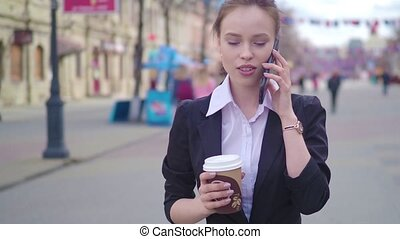 Young successful businesswoman using smart phone in city downtown, professional female employer talking with business partner drinking coffee. Business district skyscrapers in background