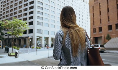 Young successful businesswoman walking through the financial...