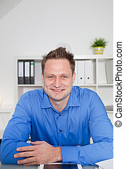 Young successful employee sitting at his desk
