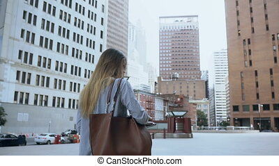 Young successful female holding the documents and walking to...