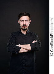 Young successful man against black background