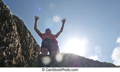 Young successful man standing on the edge of rock rises his...