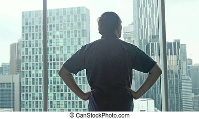 Young successful rich man comes to the window and admire the...
