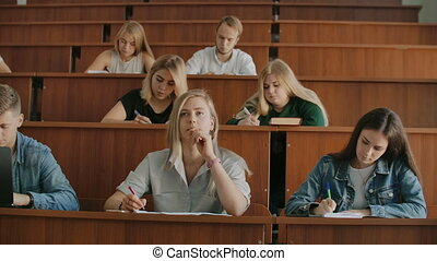 Young successful students in a large university class listen...