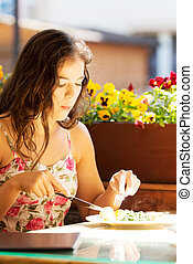 Young summer woman eating dinner.