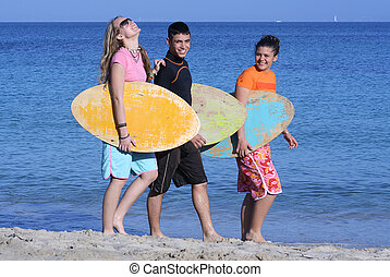 young surfers walking along beach happy and smiling