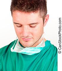 Young surgeon looking down - Young surgeon with mask looking...