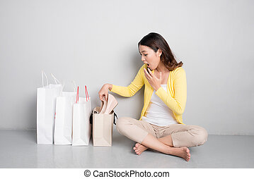 Young surprised asian woman sitting besides row of shopping bags, happy with new shoes