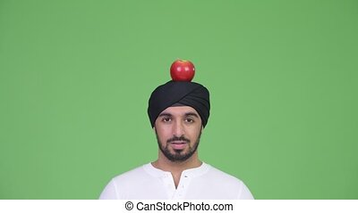 Young surprised bearded Indian man wearing turban with apple...