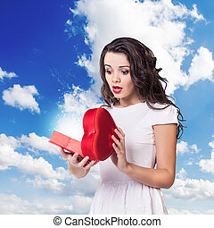 Young surprised woman holds open heart box