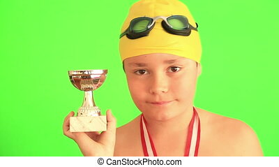 Young swimmer holding a champion trophy